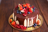Birthday cake with cream and chocolate, fresh fruit and berries slide.
