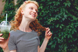 Happy ginger girl with curly hair and cocktail tinted photo