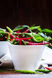 Red and green chili peppers in white bowls. Vintage wooden backg