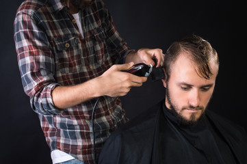 Barber shaves the hair to the client. On a black background.