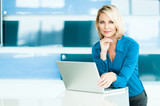 Blond Businesswoman in Modern Office with Laptop Computer - 124041122