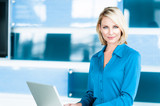 Blond Businesswoman in Modern Office with Laptop Computer