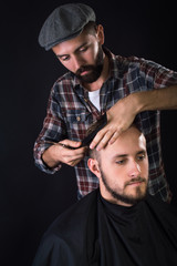 Barber cuts client with scissors hair. On a black background.
