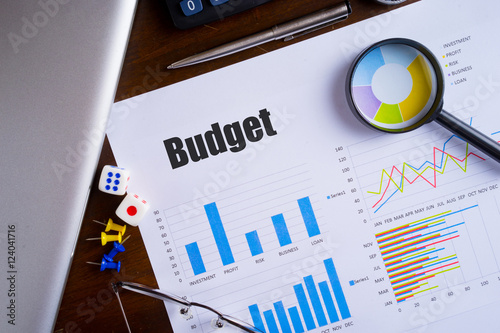 "Poster ""Budget"" text on paper sheet with magnifying glass on chart, dice, spectacles, p"