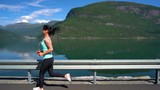 Woman jogging outdoors. Norwegian fjord.