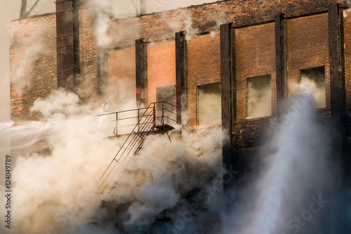 Poster Chicago Smoke enveloping staircase while firefighters spray water into burning building downtown Chicago
