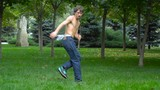 Young man dancing hip-hop and break dance in the park on the green grass.