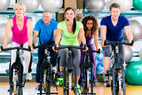 Fototapety Fitness group of men and women spinning of bike in gym