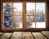 Blick aus dem Fenster einer Holzhütte im Winter