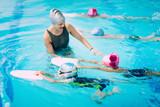Fototapety Kids having a race in swimming class