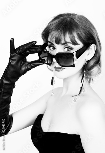 Beauty retro female model with professional makeup in a long leather gloves, holding over size sunglasses. black and white © sandyche