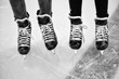Two pair of legs in ice hockey skates in black and white