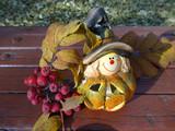 Фигурка символа Хеллоуина на деревянной скамейке на фоне осенних листьев