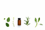 Bottle of essential oil with  fresh herbal sage, rosemary, thyme - 124087525