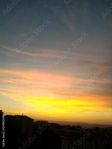 Poster Cielo giallo rosa e azzurro sulle case all'alba