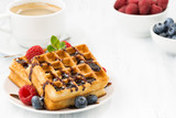 traditional sweet waffles with chocolate and berries, closeup