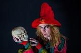 eine Hexe hält einen Schädel in der Hand