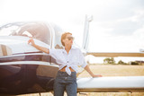 Beautiful young woman standing near private plane