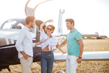 Cheerful young friends standing and talking on runway near airplane