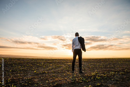 Businessman in elegant suit with his jacket hanging in field over sunset background