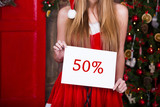 Woman in red dress with discount sign over christmas tree background. Xmas, holidays and people concept