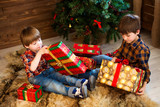 Two boys, opening presents on Christmas.