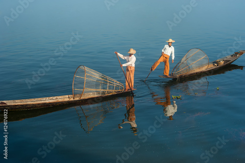Burmese fisherman on bamboo boat catching fish in traditional way with handmade net Poster