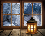 Weihnachten - Laterne vor dem Fenster einer Holzhütte in verschneitem Winterwald - 124180518