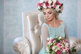 Gorgeous bride in wedding blue dress flowers wreath and bouqute