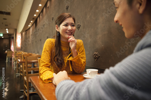 Young couple is holding hands in a cafe Poster