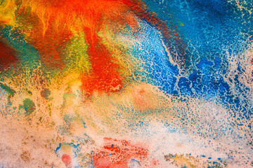 dried streaks of multicolored paint with cracks