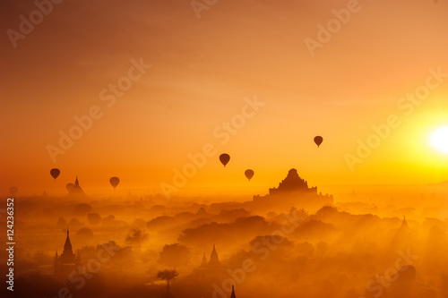 Amazing misty sunrise colors and balloons silhouettes over ancient Dhammayan Gyi Pagoda Poster