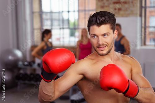 Poster mann trainiert mit boxhandschuhen in einem club