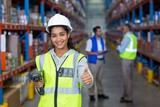 Female warehouse worker showing thumbs up sign