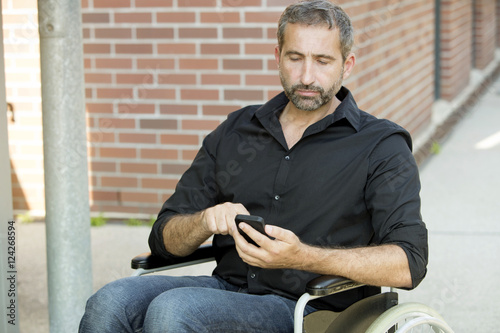 man in wheelchair texting on his phone Poster