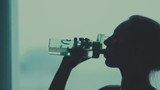 Slowmotion. Silhouette of a woman drinking water out of a water bottle. Completion of training. The final workout. Pause. Close-up of a dark profile of a woman drinking water.