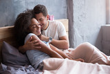 Young couple embracing in their bed tenderly
