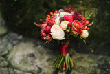 Wedding bouquet of red and white flowers and berries on old stone with moss on it. Shallow focus. - 124275366