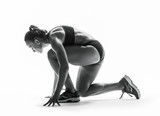 Young fitness woman preparing for a run. Fit female athlete ready for a sprint. Isolated