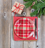 Xmas dinner setting with evergreen branches and gift box on wood