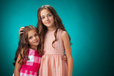 The two cheerful little girls on orange background
