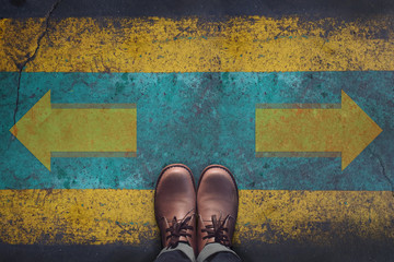 Top view, Male with Leather Shoes, Arrow Sign on Grunge Dirty Concrete Floor Background, Making Decision at the Crossroad