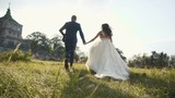 Wedding Couple Runing in grass Field near Castle on Sunset