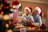 children and father making Christmas cookies.