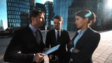 4k. Ultra HD. POV. Your big chance attention calling. Three Young successful attractive businessmen and businesswoman in suits give mobile phone to You. Modern glass building at the bg. Sunny day