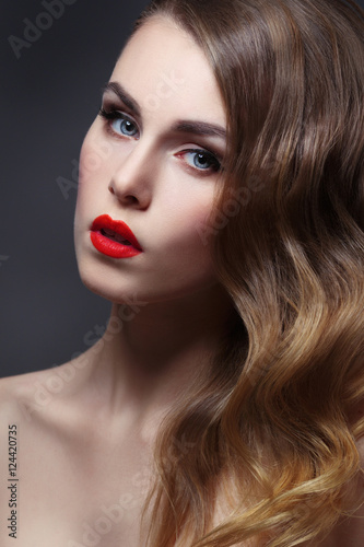 Fashion beauty portrait of gorgeous girl with curls and red lipstick in the style of Hollywood on a black background © ksi