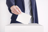 Voting. Man putting a ballot into a voting box. - 124425769