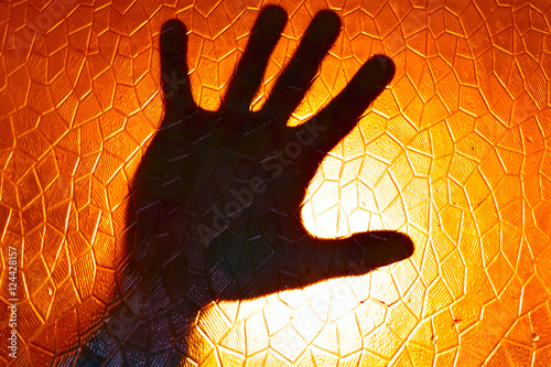 Poster Hand Silhouette on Fire Orange Color Background stained glass with geometric pat
