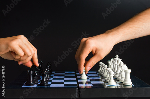Fotografiet Women's and men's hand playing chess. On a black background.