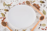 белая тарелка и специи на белом фоне